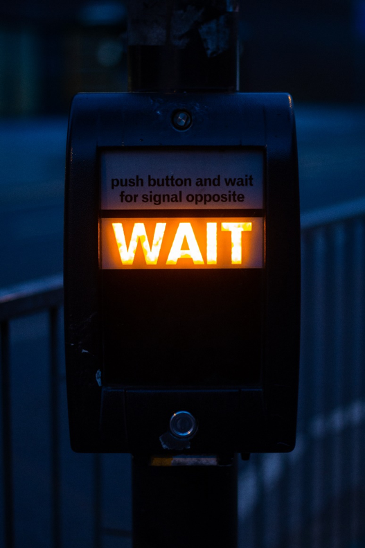 "An image of a pedestrian sign that says ""Wait"" in lit orange letters."
