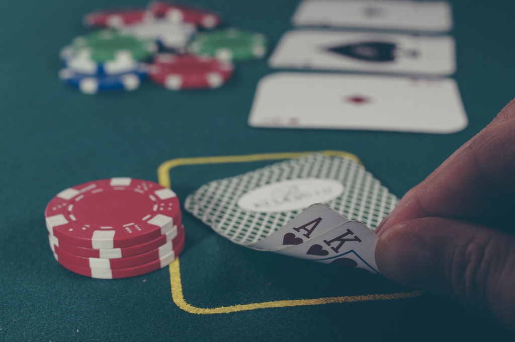 A hand pulling up the corner of two cars in a game of poker, showing an ace and king of hearts.