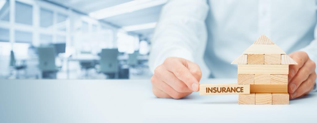 Person pushing jenga block marked 'insurance' into place in a jenga tower shaped like a house